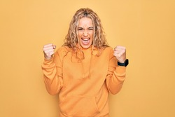 Young beautiful blonde sporty woman wearing casual sweatshirt over yellow background angry and mad raising fists frustrated and furious while shouting with anger. Rage and aggressive concept.
