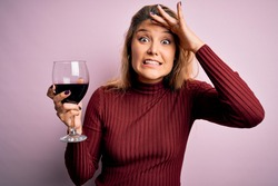 Young beautiful blonde woman drinking glasse of red wine over isolated pink background stressed with hand on head, shocked with shame and surprise face, angry and frustrated. Fear and upset