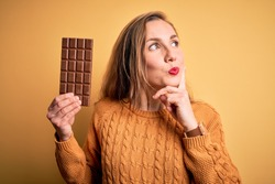 Young beautiful blonde woman holding chocolate bar standing over isolated yellow background serious face thinking about question, very confused idea