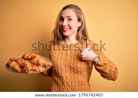 Young beautiful blonde woman holding plate with croissants over isolated yellow background happy with big smile doing ok sign, thumb up with fingers, excellent sign Stock fotó ©