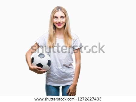 5fb40d7d2 Young beautiful blonde woman holding soccer ball over isolated background  with a happy face standing and