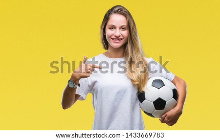Young beautiful blonde woman holding soccer ball over isolated background with surprise face pointing finger to himself