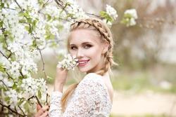 Young beautiful blonde woman in blooming garden. Bride.