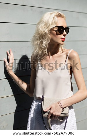 Young beautiful blonde woman in light dress with clutch and sun glasses posing outside with wooden wall in background. Fashion accessories. Streetstyle summer spring photo #582479086