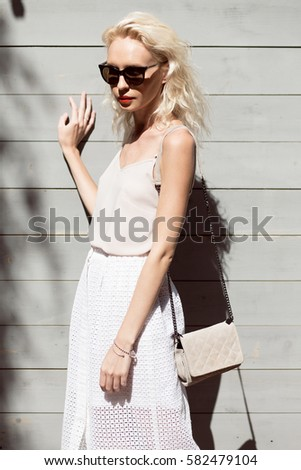 Young beautiful blonde woman in light dress with clutch and sun glasses posing outside with wooden wall in background. Fashion accessories. Streetstyle summer spring photo #582479104