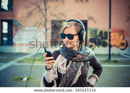 young beautiful blonde woman listening to music in the city