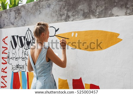 Stock Photo Young beautiful blonde woman painting the wall, street art in process, street artist - painter