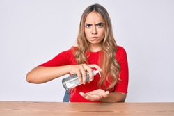 Young beautiful blonde woman sitting on the table cleaning hands using sanitizer gel skeptic and nervous, frowning upset because of problem. negative person.