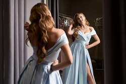 Young beautiful blonde woman wearing an off-the-shoulder full-length sky blue satin slit prom ball gown. Model looking in mirror.