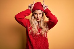 Young beautiful blonde woman wearing casual sweater and wool cap over white background doing funny gesture with finger over head as bull horns
