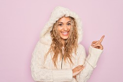 Young beautiful blonde woman wearing casual sweater with hood over isolated pink background with a big smile on face, pointing with hand and finger to the side looking at the camera.
