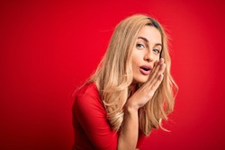 Young beautiful blonde woman wearing casual t-shirt standing over isolated red background hand on mouth telling secret rumor, whispering malicious talk conversation