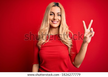 Young beautiful blonde woman wearing casual t-shirt standing over isolated red background showing and pointing up with fingers number two while smiling confident and happy. Photo stock ©