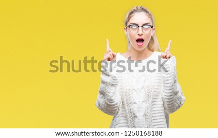 Young beautiful blonde woman wearing glasses over isolated background amazed and surprised looking up and pointing with fingers and raised arms. #1250168188