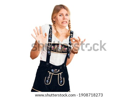 Young beautiful blonde woman wearing oktoberfest dress disgusted expression, displeased and fearful doing disgust face because aversion reaction.  ストックフォト ©