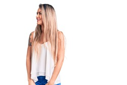 Young beautiful blonde woman wearing sleeveless t-shirt looking away to side with smile on face, natural expression. laughing confident.