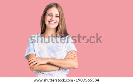 Young beautiful blonde woman wearing tye die tshirt happy face smiling with crossed arms looking at the camera. positive person.  Foto stock ©