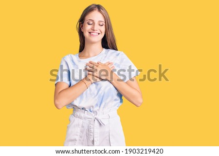 Young beautiful blonde woman wearing tye die tshirt smiling with hands on chest with closed eyes and grateful gesture on face. health concept.  Сток-фото ©