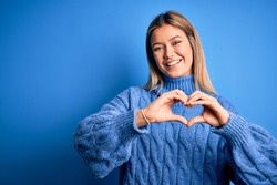 Young beautiful blonde woman wearing winter wool sweater over blue isolated background smiling in love doing heart symbol shape with hands. Romantic concept.