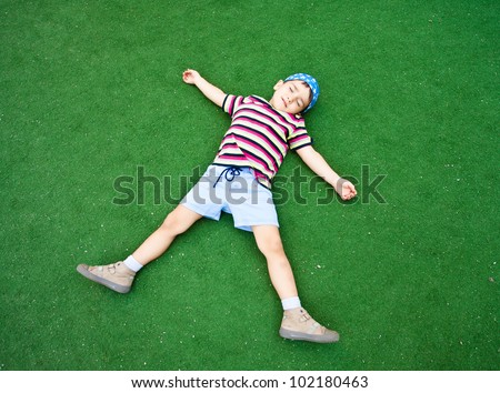 Young beautiful boy laying on plastic green grass pretending sleep in starlike pose