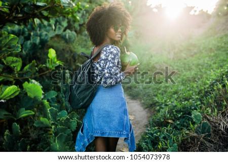 Young beautiful Brazilian girl staying on beach in Rio de Janeiro, laughing and drinks coconut
