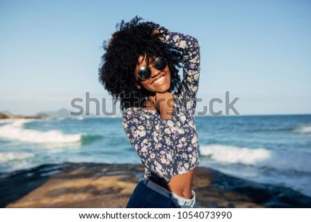 Young beautiful Brazilian girl staying on beach in Rio de Janeiro on warm sunny  and laughing