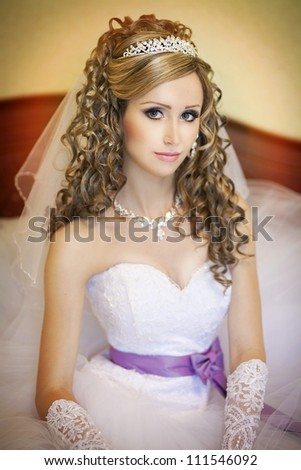 young beautiful bride at home waiting for groom. slim woman in luxury wedding dress in diamond jewelry and tiara posing. Sexy smiling bride with wedding makeup looks happy.series. autumn