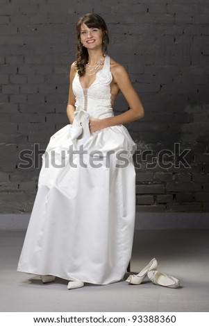 Young, beautiful bride posing in wedding dress before a brick wall