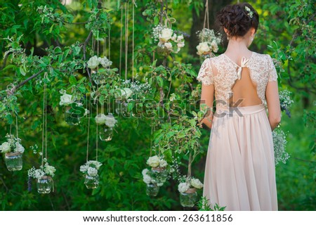Young beautiful bride standing with his back amid banks decorated with roses tree,decor,concept,wedding decorations