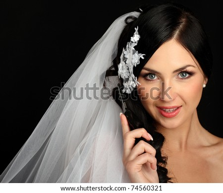 Young beautiful bride talking on mobile phone, isolated on black, studio shot