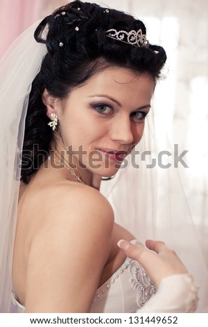 Young beautiful bride waits for groom near the window. Beautiful Bride lit by sunlight from a window. beautiful young bride standing beside a large window waiting and plays her veil