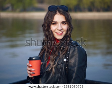 01ac0229cc48 Young beautiful brown-haired curly teen student girl in in red dress  leather jacket having