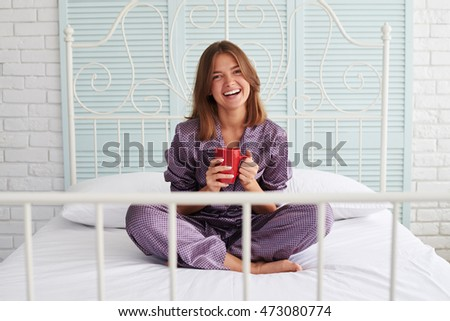 Young beautiful brown-haired female is sitting on bed with a cup of coffee wearing pajamas in domestic atmosphere