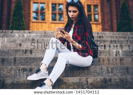 Young beautiful brunette blogger viewing photos in social network via application on cellphone while sitting at street.Cute hipster girl sending email message using modern phone and 4G internet
