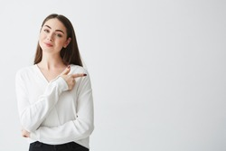 Young beautiful brunette businesswoman smiling looking at camera pointing finger in side over white background.