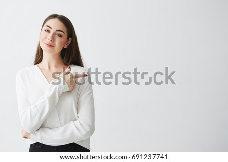Shutterstock Young beautiful brunette businesswoman smiling looking at camera pointing finger in side over white background.