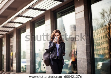 young beautiful brunette drinking coffee walking around the city.leather jacket,urban backpack , bright red lips Beautiful brunette or student enjoying weekends #600421376
