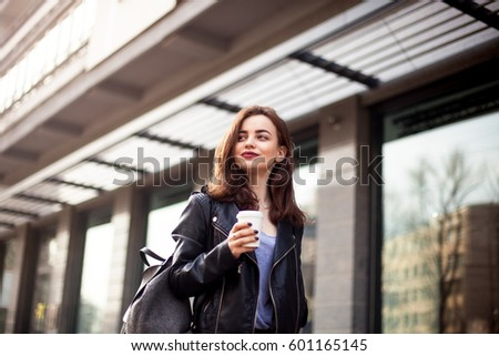 young beautiful brunette drinking coffee walking around the city.leather jacket,urban backpack , bright red lips Posing against the window of the boutique Model looking aside