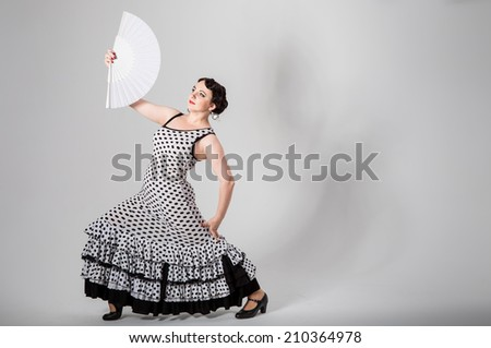 young beautiful brunette female spanish flamenco dancer in black and white flamenco dress dancing with white fan in her hands in studio on gray background