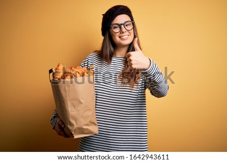 Young beautiful brunette french woman wearing beret holding bag with homemade croissants happy with big smile doing ok sign, thumb up with fingers, excellent sign Stock fotó ©