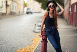 young beautiful brunette girl in a hat, sunglasses, t-shirt and jeans, walking on the ancient city, holding hand hat for fear of losing it