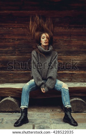 young beautiful brunette girl in a warm knitted sweater in jeans and boots posing on the street, on the street porttrait, to close the model