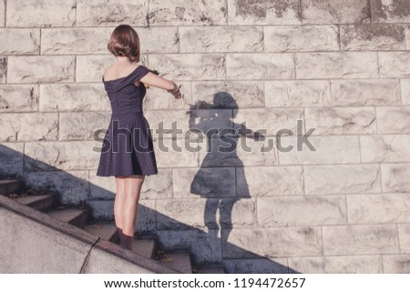 Young beautiful brunette girl in blue dress dancing with her shadow on stone wall background, concept of inspiration, enthusiasm and aspiration #1194472657