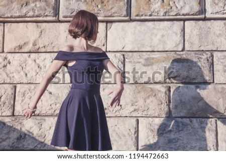 Young beautiful brunette girl in blue dress dancing with her shadow on stone wall background, concept of inspiration, enthusiasm and aspiration #1194472663