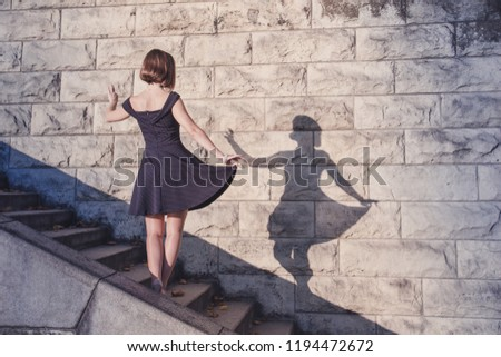 Young beautiful brunette girl in blue dress dancing with her shadow on stone wall background, concept of inspiration, enthusiasm and aspiration #1194472672