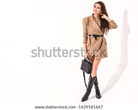 Young beautiful brunette girl in nice trendy summer suit clothes.Sexy carefree woman posing near white wall in studio.Fashionable model with bright evening makeup.She holds bag in hands