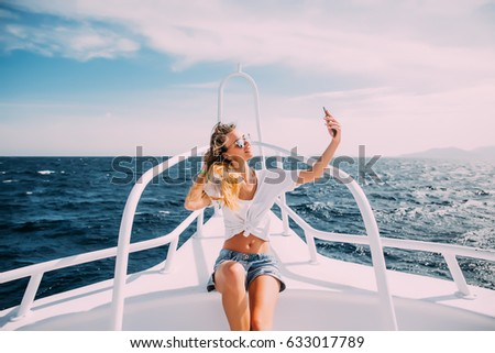 Young beautiful brunette girl making selfie using phone while sitting on the luxury yacht