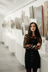 Young beautiful brunette girl standing in a gallery contemplating paintings artworks displayed on gallery walls. Art gallery.