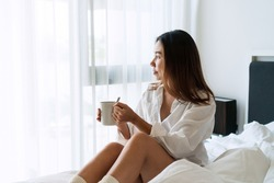 Young beautiful brunette hair woman in white shirt pajamas drinking coffee while sitting on the bed in the morning.