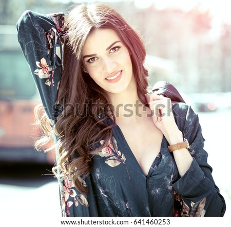 Young beautiful brunette in 20s wearing fashionable modern clothes on the streets of Sarajevo, Bosnia during spring blossom day. Toned image. #641460253